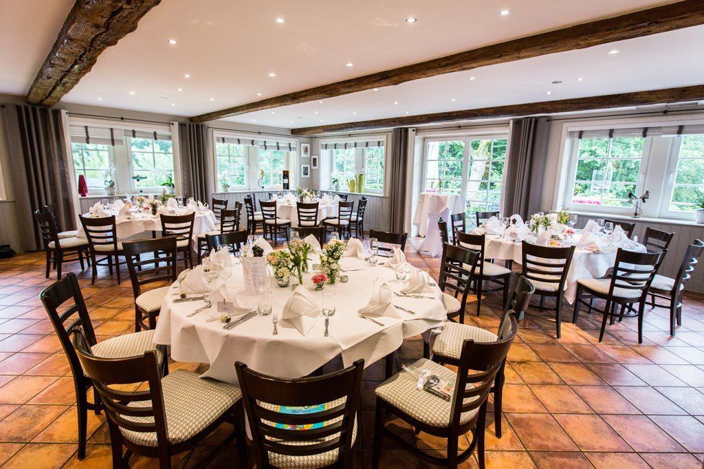 Das Gartenzimmer mit den runden Tischen und Zugang zur Terrasse ist ein perfekter Hochzeitsraum