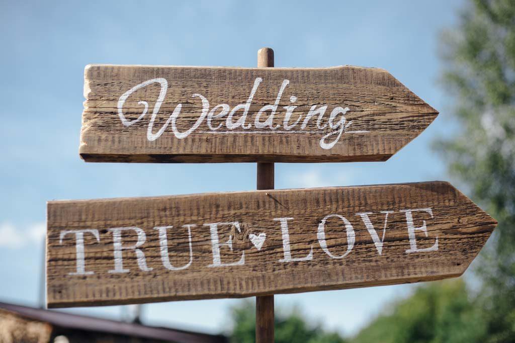 Holzschild zeigt in Richtung Hochzeit und wahrer Liebe