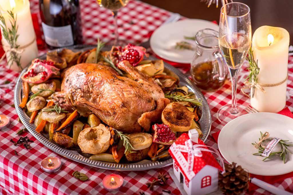 Weihnachtsfeier mit gedecktem Tisch, einer Hütte aus Lebkuchen und Weihnachtsessen