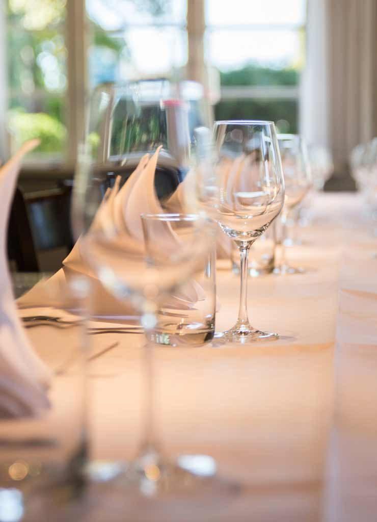 Gedeckter Tisch mit Weingläsern und Tellern für ein Menü